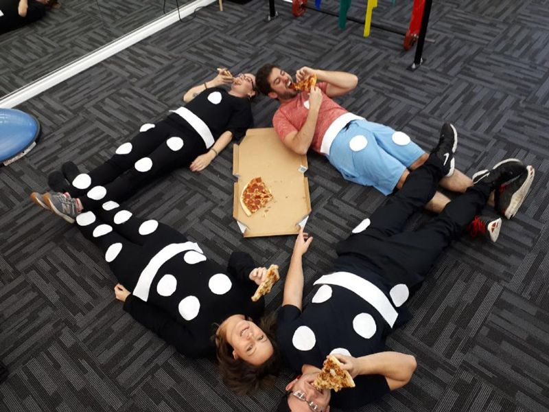 4 people lying on the floor and having pizza